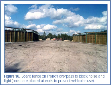 Figure 16. Board fence on French overpass to block noise and light (rocks are placed at ends to prevent vehicular use).